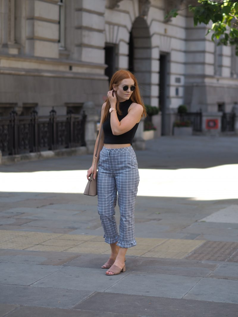 City of London wearing Topshop checked trousers, a black crop top and New look muted pink mules